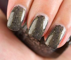 "SpaRitual Conglomerate Nail Lacquer- described as a ""charcoal rock glitter infused with rhyolite."" This has a murky gray base with olive green shimmer and circular black and light gray flecks. It's the mixture of shimmer and glitter that makes this unlike other polish"