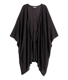 Poncho in a soft, fine knit with 3/4-length sleeves, a gently rounded hem and closed sides with slits.