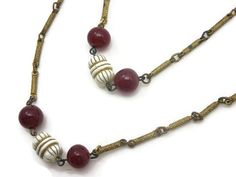 A beautiful vintage brass link necklace, with two strands and art glass accent beads in white and marsala red.  Missing one red glass bead, I have