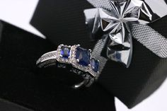 This is a gorgeous 2.3ct Radiant cut Sapphire and CZ engagement ring.  Ring Details:  Total Carat Weight: Approx. 2.30ct Gemstone: Trio of Lab Blue Sapphires Center Stone Cut: Radiant Side stones: Cubic zirconia Side Stone Cut: Round Band Width: 2.3 mm Metal: Platinum Rhodium plated over lead free alloy  Quick note about the pictures before I tell you more about the ring - All the pictures are of the actual ring and since we arent professional photographers, the black you see on the ring is…