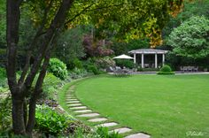 A bluestone path leads past a perennial border, through a large lawn, and to a pool and pool house.  A Planters design.  Atlanta, GA
