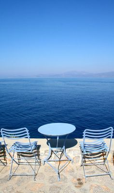 Blue chairs, facing blue water and sky, on the island of Hydra, Greece