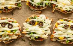 Mini pizzas get a spooky twist for a pre-trick-or-treating dinner that's quick and delicious. Create mummy faces on English muffins with kale, bell peppers and string cheese. Quick tip: Toast the muffins before you assemble the pizzas to keep them crisp. Fete Halloween, Halloween Food For Party, Halloween Treats, Happy Halloween, Halloween Foods, Halloween Dinner, Halloween Night, Fall Recipes, Holiday Recipes