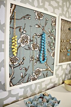 Necklace holder: fabric covered cork in a frame, using pretty pins to hold necklaces