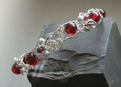 Bloody Forest - silver plated wire wrapped bracelet with cherry amber and garnet beads. $32.00, via Etsy.