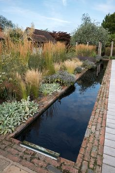 The reflection pool spans the entire length of the kitchen, reflecting the passing clouds. An herbaceous border of grasses and perennials provides year-round interest. Photo by: Elliot Hook.