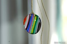 Fused glass, striped pendant.  Eerin Vink is an illustrator and artist. She also makes jewelry out of wood, glass, gemstones and silver. You can find this artist on Etsy: https://www.etsy.com/shop/EerinVinkArts.