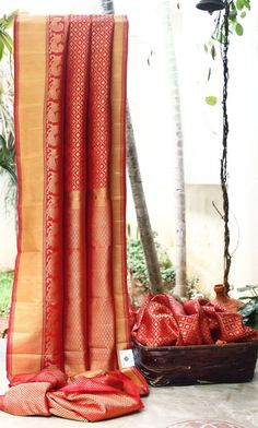 DAZZLING RED WITH GOLD ZARI CHECKERED ALL OVER HAS INTRICATELY WOVEN RED WITH GOLD ZARI BORDER AND PALLU MAKING THE SAREE TIMELESS PIECE.