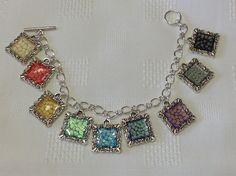 Pebeo fantasy prisme paint samples in cabachon frames. Turned into charm bracelet.