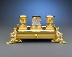 "Regency Ormolu Inkstand Concealing A Mahogany-Lined Double Drawer With Impressive Lion's Head Handles In Its Rectangular Base, Four Imposing Sphinxes Support Each Corner, Two Krater-Vase Inkports Raised On Clustered Sphinx Paws - Inscribed ""Week's R T Museum Titchbore St'.   c.1800   -   M.S. Rau Antiques"