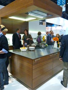+ARTESIO Kitchen by Poggenpohl in walnut finish - On display at the KBIS 2012 Show in Chicago. With it's innovative ceiling elements, the 'function arch' facilitates power management and provides accommodation for audio system, ventilation extractor, or indirect LED lighting.