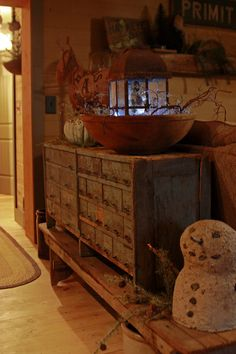 Old Bench & Primitive Cupboard...light by a rustic lantern...prim grungy snowman.