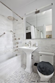 A contemporary bathroom with white tile, a pedestal sink and a rain shower head. Click to get a clearer picture of the costs associated with installing a new shower or tub.