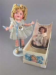 12' IDEAL COMPOSITION SHIRLEY TEMPLE IN ORIGINAL TAGGED PLEATED ORGANDY DRESS AND BOX. ORIGINAL TAGGED DRESS CLEAN AND CRISP.