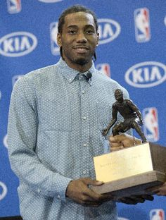 de2ba4c6971a50 San Antonio Spurs  Kawhi Leonard holds his trophy during a news conference  after he was named the NBA defensive player of the year