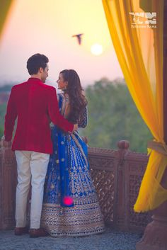 sunset portrait , velvet jacket on groom , blue lehenga , royal blue lehenga