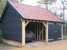 Eine schwarze Holzgarage mit dem Carport. Finden Sie mehr Information auf www.pineca.de/holzgaragen/