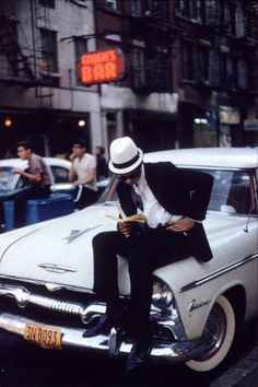Ernst Haas - A man sitting on a Plymouth car and reading a book in New York City., 1962