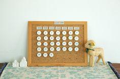 身近な素材でできるアイデアカレンダー。数字部分はペットボトルのふたを再利用しています。/手作りカレンダー(「はんど&はあと」2012年1月号)