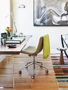 The custom desk features a reclaimed wooden top and Plexiglas legs, creating the illusion of a floating desk. Bright accents, like the area rug, bring a vibrant, creative touch to the home office.