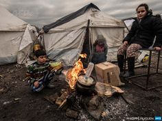 """France, Grande-Synthe : Young migrants get warm around a  brazier in the migrants camp of Grande-Synthe, near Dunkirk, on January  20, 2016, where almost some 2,500 migrants and refugees live, mostly  Iraqi Kurds and Syryans. Authorities in the northern French  port of Calais were struggling to move hundreds of migrants into  refitted shipping containers ahead of plans to bulldoze part of the  notorious """"Jungle"""" camp. There wre also attempts to relocate 2,500  migrants camped som..."""