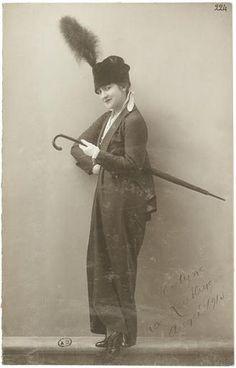 Manon Jocelyne en pied de trois-quarts face avec un parapluie et un chapeau, 1913.