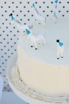 cute cake with white horses and blue party hats