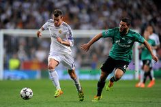 Gareth Bale is pursued by Sead Kolasinac during the UEFA Champions League round of 16, second leg match between Real Madrid and FC Schalke 04 at Estadio Santiago Bernabéu on March 18, 2014 in Madrid, Spain.