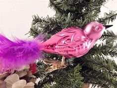 """Beautiful glass bird Christmas tree ornament Pink bird with purple feather tail Iridescent glitter accents Tail tip to beak measures approximately 6 1/2""""  3 1/2"""" h including spring and clip, 1 1/4"""" w 1/2"""" spring connects bird to gold metal ..."""