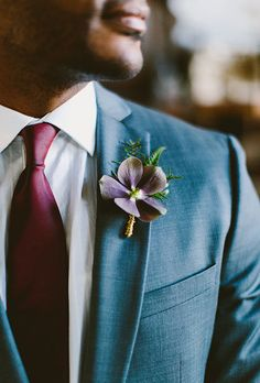 Brides.com: . A purple clematis boutonniere created by Sebesta Design.