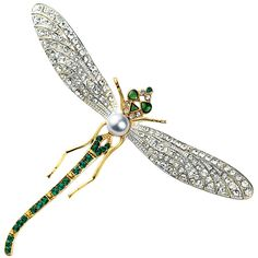 """Russian Dragonfly Pin features 22k Gold and silver, with a freshwater pearl and Swarovski crystals adapted from the Moscow Kremlin jewels. Rose-cut diamonds are applied in lacy plique-à-jour mountings to create the illusion of transparency. The insect's gold body contains a single large pearl, while emeralds from the Ural Mountains form its eyes and tail. 2.25 L x 3"""" wide $90"""