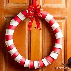 A candy cane striped DIY wreath made of paper coffee cups! Click for how-to tips and more DIY Christmas wreath ideas.
