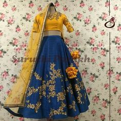 One of our favoutite designs in mesmerising combination of mustard and teal blue. A treat to the eyes and a true head turner. Beautiful blue color designer lehenga and mustard color designer cro top with hand embroidery work on yoke and sleeves. Half Saree Designs, Choli Designs, Lehenga Designs, Blouse Designs, Half Saree Lehenga, Blue Lehenga, Lehenga Gown, Lehenga Blouse, Anarkali Dress