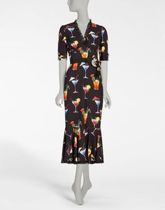 <i>The Spring-Summer 2017 is a journey towards an imaginary Italian Tropic, where the icons traditionally associated with Italy, like bread, pasta and good luck charms are merged with a holiday atmosphere, punctuated by cocktails, ice cream and sequins.</i><br><br>Cady sheath dress with cocktail print and flounce hem featuring decorative bejeweled button embellishment at the back and a crystal-adorned bow at the front:<br>• Front V-neck with lace trim<br&...