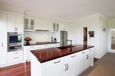 Smart finish includes brick walls in the scullery and brick-style tile detail on the splashback behind the gas hobs. It cleverly maintains the American theme and enhances this kitchen's traditional country style.