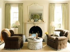 Perfect symmetry - tufted reading chairs with contrast welting, ottoman, garden stools, swing-arm reading lamps, hydrangeas on the mantle with a pair of hurricane candlesticks and coral - Ashley Whittaker