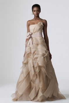 Pale nude strapless full A-line tissue organza gown with asymmetrically draped bias tiered origami skirt, back bows, and nude grosgrain bow at natural waist