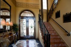 This ornate Tuscan-style foyer has gorgeous tile floors, a tile staircase, and gorgeous carved side table with a marble top.