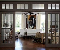 Glass French Doors Like windows, doors are a key part of any wall's composition. Here, beautiful French doors separate the living room from a large foyer, while still letting light flow freely between rooms. Incorporating a pair of French doors into a living space allows you to add a little old-fashioned charm.