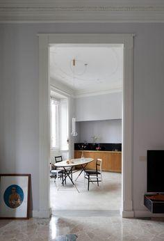 Dal soggiorno si intravede la cucina-pranzo dietro lo stipite in legno  realizzato su disegno  di Pietro Russo. Suo anche il tavolo Piuma co...