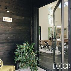 A entrada da morada é marcada por uma porta envidraçada contrastando com a madeira escura