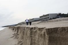 """Un buen ejemplo de cohesión """"aparente"""".  2013.10.18 - People walk past The Royal Atlantic Beach Resort where it faces the eroded beach in Montauk, Suffolk County. Superstorm Sandy shocked new life into a decades-old federal plan to fortify Long Island's southern coastline. (John Taggart for The Wall Street Journal)"""
