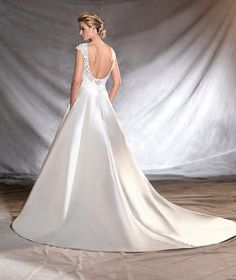 OSVINA - Distinguished mikado wedding dress with an aristocratic air. Classic fitted waist, round neck and princess skirt. The detail: gemstone and embroidered thread decorate the bodice.