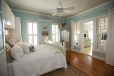 Gorgeous aqua and white cottage chic bedroom. Love the narrow air conditioner in the wall aimed at the ceiling fan--it doesn't block the beautiful light coming in from the windows. (by Jeanette Van Wicklen Design via Erin at House of Turquoise.)