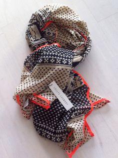 Lollys Laundry Penny tørklæde er i en fin og let kvalitet. Tørklædet er aflangt og i nogle flotte farver, mørkeblå og neon på beige baggrund. Tørklædet er med et flot mønster, en cool påsyet i neon.