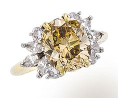 A colored diamond and diamond ring, mounted by Cartier centering an oval-cut brown diamond, weighing 3.84 carats, with marquise and circular-cut diamond cluster shoulders; signed Cartier; mounted in eighteen karat gold and platinum.