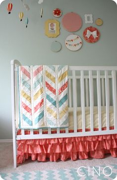 nursery with sherbet like colors. More embroidery hoops with fabric as artwork. Also, cute ruffled crib skirt and hot air balloon mobile.