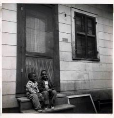 Louis Armstrong sitting on a stoop as a little boy on Jane Pl in New Orleans.