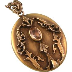 Art Nouveau large oval locket with ornate decoration, glass citrine, and fanciful creature bail, signed GNS Co, in gilt brass.  George Nathaniel  $300