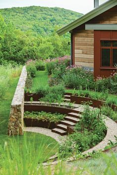 Fieldstone retaining walls wrap the herb and vegetable garden amphitheater at Iron Mountain House, and Cor-Ten steel bands filled with crushed stone create a stepped terrace.
